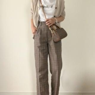 カーディガンとロゴTシャツにチェックテーパードパンツを履いた女性