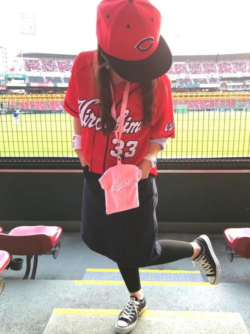 赤のユニフォームとキャップにネイビーのスカートを合わせるカープ女子コーデ