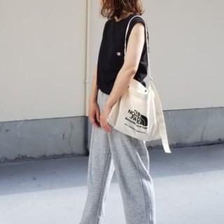 黒ノースリーブTシャツとワイドスウェットパンツにビーチサンダルを履いた女性