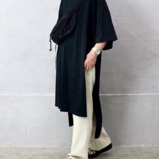 ブラックTシャツワンピとホワイトパンツにブラックサンダルを履いた女性