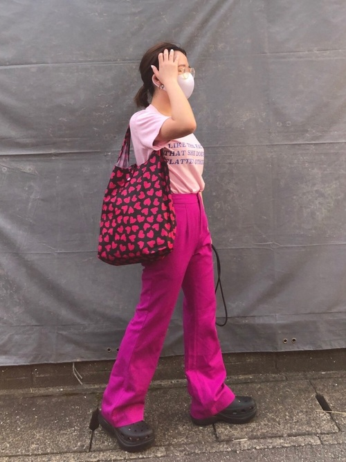 ピンクTシャツとピンクストレートパンツに黒サンダルを履いた女性