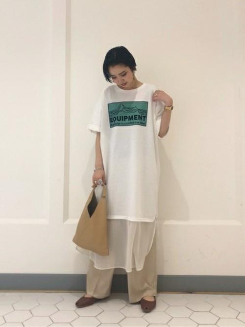 ロゴスウェットワンピースとワイドタックパンツにオープントゥフラットシューズを履いた女性