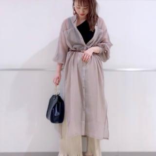 シアーロングシャツワンピースとアシメタンクトップにプリーツイージーパンツを履いた女性