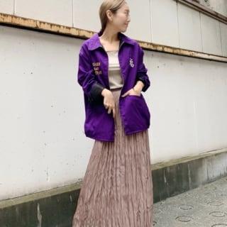 パープルベトジャンとフィラメントサテンスカートに黒革ブーツを履いた女性