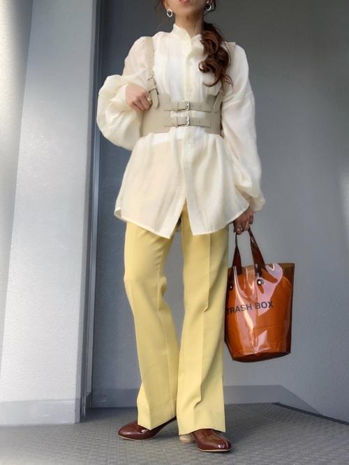 ヘンリーネックシアーシャツとレモンイエローパンツにブラウンエナメルパンプスを履いた女性