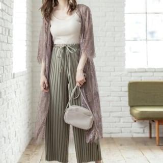 フラワーレースカーディガンとプリーツパンツにブラウンミュールパンプスを履いた女性
