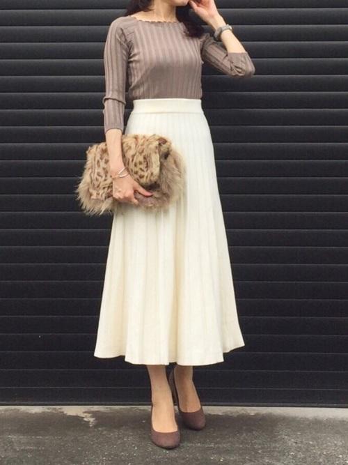 ブラウン7分丈ニットと白フレアロングスカートにブラウンチャンキーヒールパンプスを履いた女性