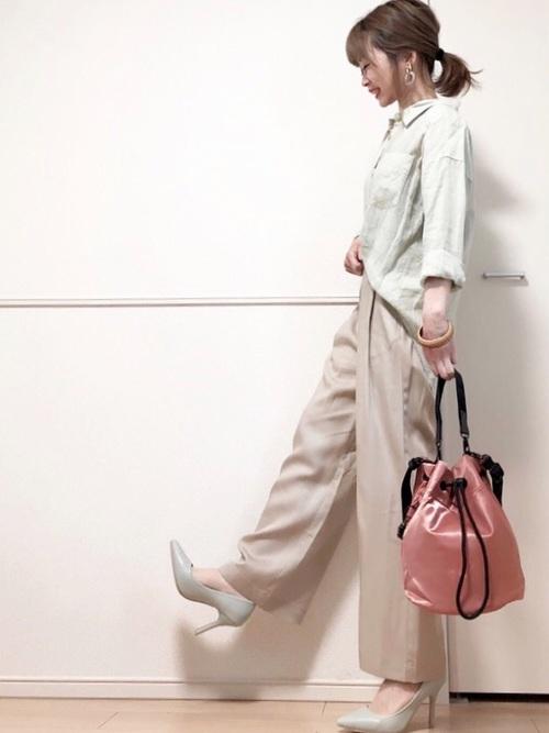 ミントフロントインカラーシャツとベージュイージーパンツにミントパンプスを履いた女性