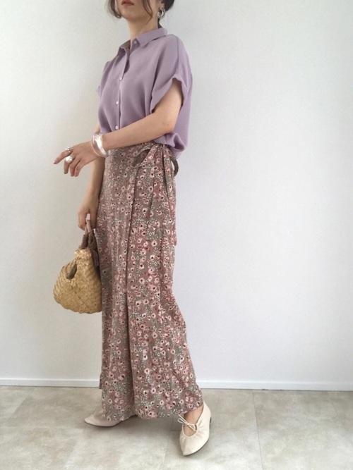 ラベンダーカラーシャツとピンク花柄フレアーパンツにベージュバレエシューズを履いた女性