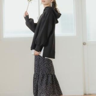 黒パーカーと黒柄切り替えスカートに黒ミドルヒールパンプスを履いた女性