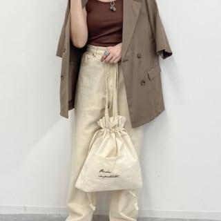 ブラウンテーラードジャケットとブラウンタンクトップに白ハイウエストデニムパンツを履いた女性