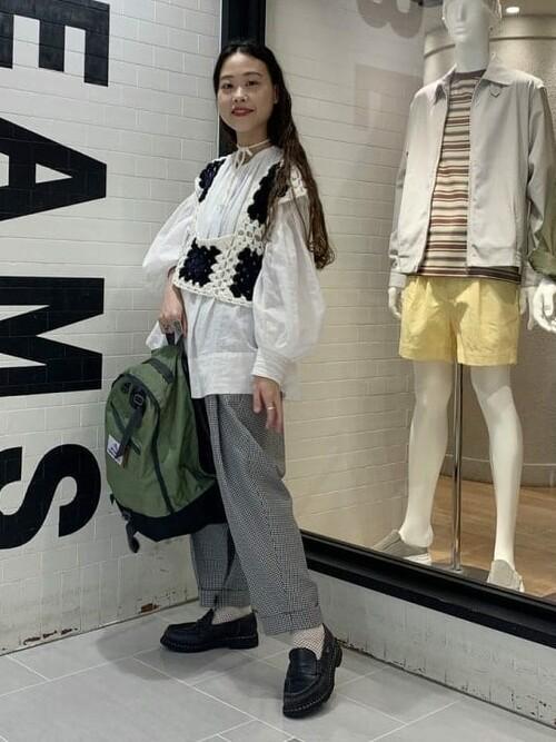 カーキビンテージデイパックリュックと白ギャザースモックにチェック柄ワンプリーツテーパードパンツを履いた女性