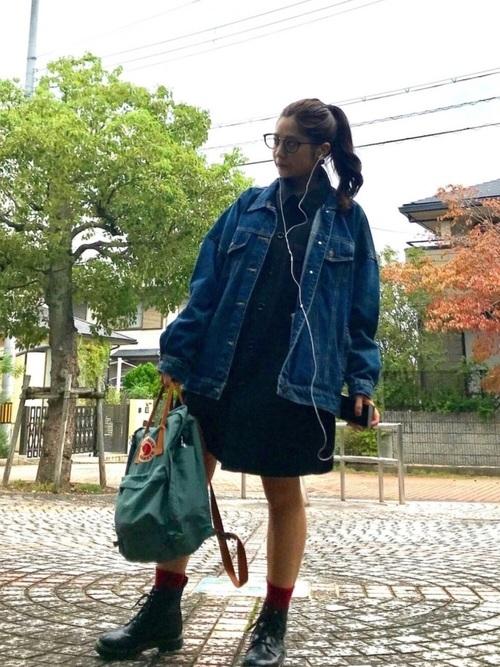 カーキスクエアキャンバスレザーリュックとビッグデニムジャケットにビッグシャツワンピースを着た女性