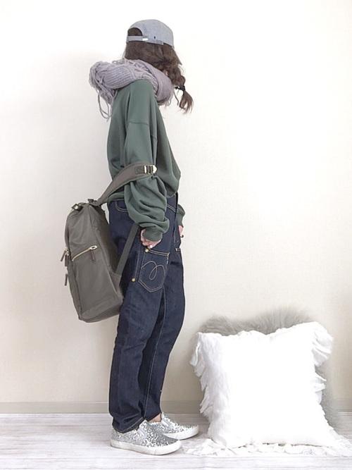 カーキナイロンリュックとカーキビッグシルエットプルオーバースウェットに後ろ前デザインテーパードデニムパンツを履いた女性
