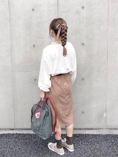 カーキスクエアキャンバスレザーリュックと白ボリューム袖スウェットにベージュギャザースカートを履いた女性