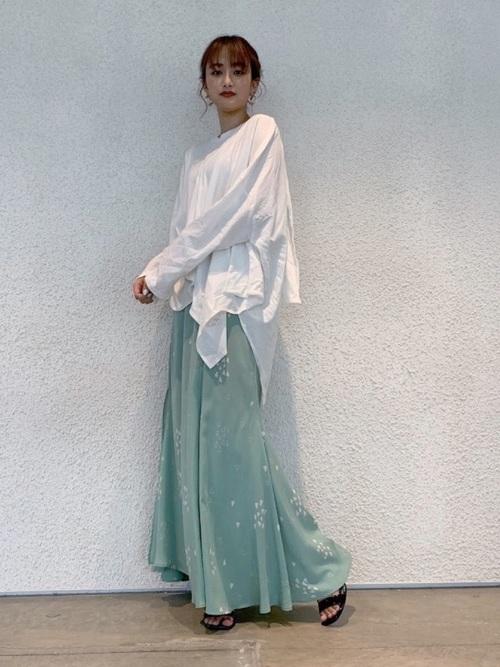 白変形Tシャツとマキシ丈スカートにサンダルを履いた女性