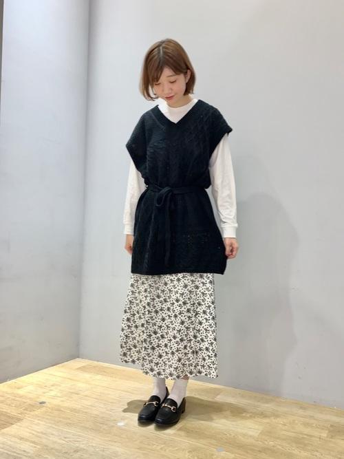 ニットベストと花柄ミモレ丈スカートにレザーローファーを履いた女性