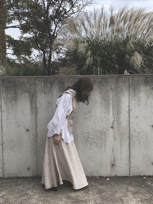 ホワイトブラウスとベージュディフォメーションレザーベストにドット柄ロングフレアスカートを履いた女性