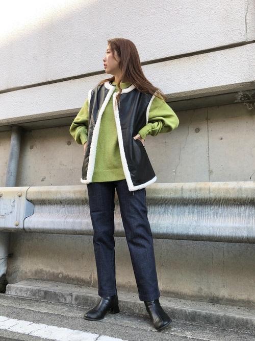 フェイクレザーベストとハイネックニットプルオーバーにハイウエストデニムパンツを履いた女性