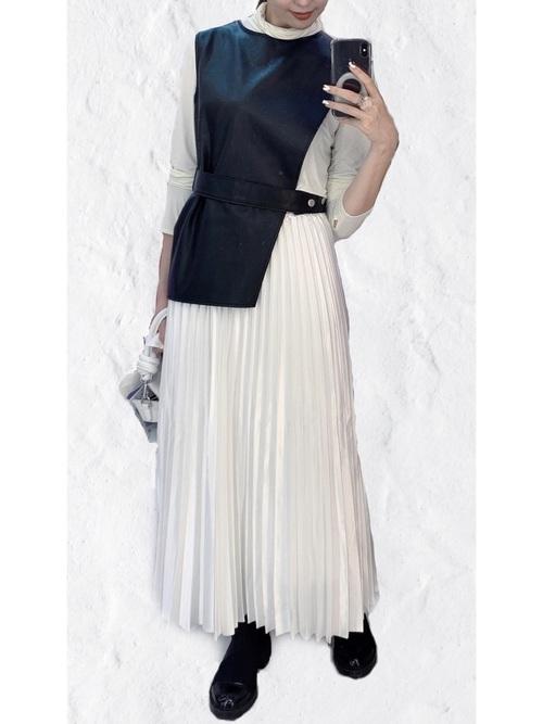 ジャージープルオーバーとディフォメーションフェイクレザーベストにサテンプリーツスカートを履いた女性