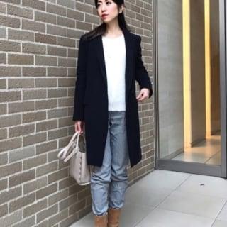 フリースボンディングコートとフェザーラメVネックプルオーバーにユニクロの暖パンを履いた女性