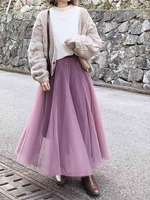 紫チュールスカートとケーブル編みカーディガンとブラウンブーツのコーデの女性