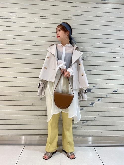 くすみホワイトショートトレンチとホワイトブラウスにイエローパンツを履いた女性