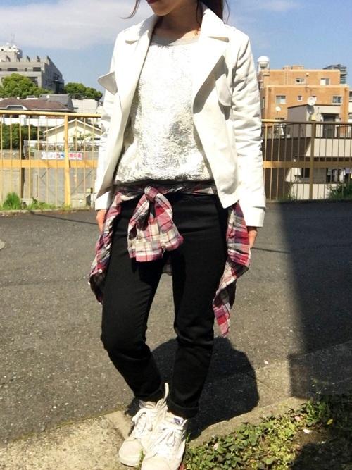白ショートトレンチと白セーターにチェック柄シャツを着た女性