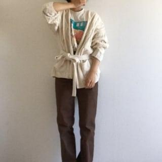 ベージュカーディガンとシュプリームのベージュTシャツにブラウンストレートパンツを履いた女性