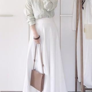 リネンシャツとマーメイドラインスカートにブラウンバングルを合わせた女性