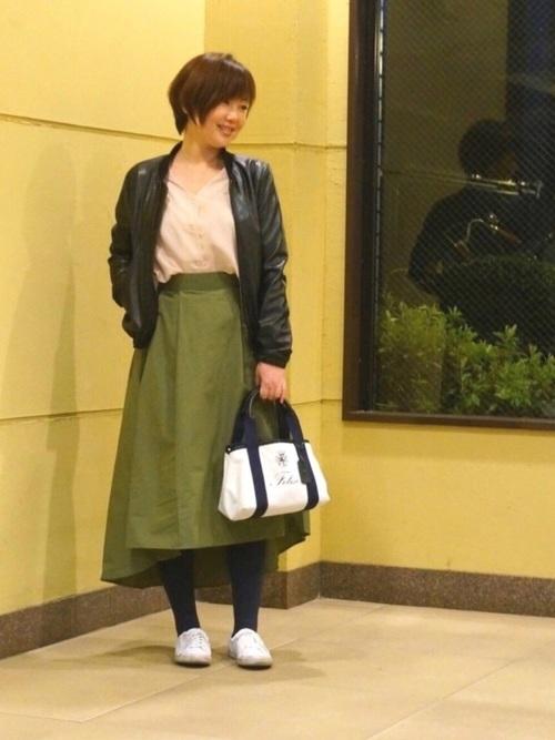 黒レザージャケットとバックテールスカートにラコステのスニーカーを履いた女性