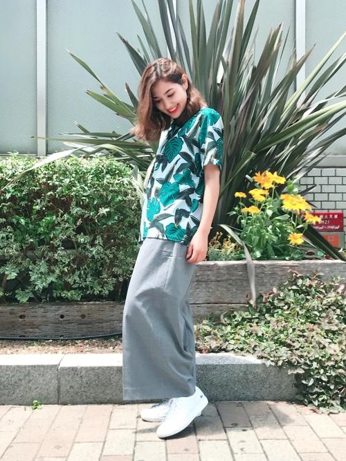 トロピカル柄ポロシャツとグレーワイドパンツにラコステのスニーカーを履いた女性