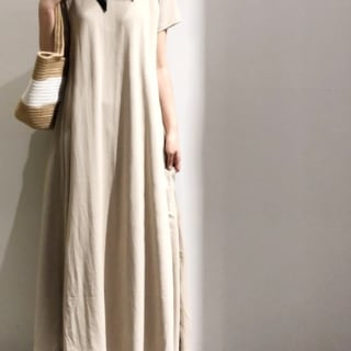 ベージュクルーネックフレアマキシワンピースとナロースカーフにマクラメフラットサンダルを履いた女性