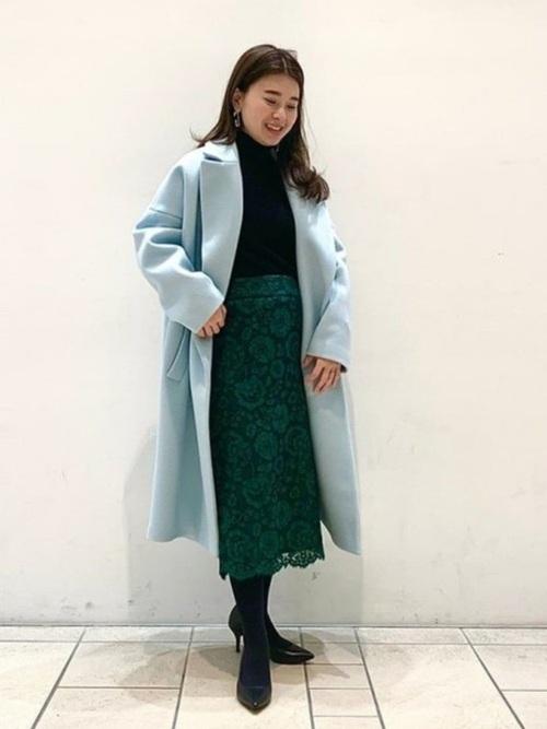 水色ロングチェスターコートと黒タートルネックニットと緑花柄レースタイトスカートのコーデの女性