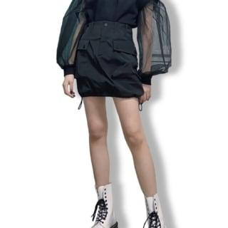 シアー素材のバルーン袖を施した黒の異素材トップに、裾が絞れるディテールの黒ミニスカートを合わせ、白のレースアップブーツを履いたコーデ
