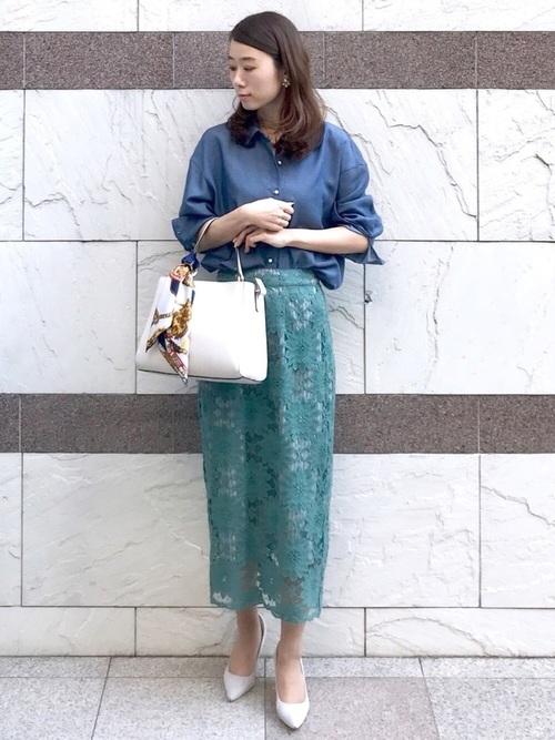 青パールボタンシャツと緑レース花柄タイトスカートとグレーパンプスのコーデの女性