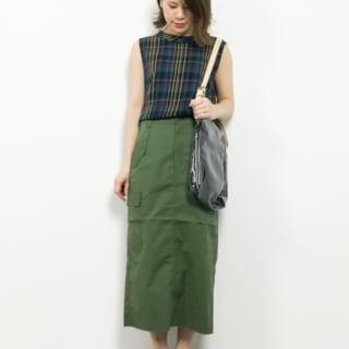 チェック柄ノースリーブブラウスと緑チノタイトスカートと黒フラットシューズのコーデの女性