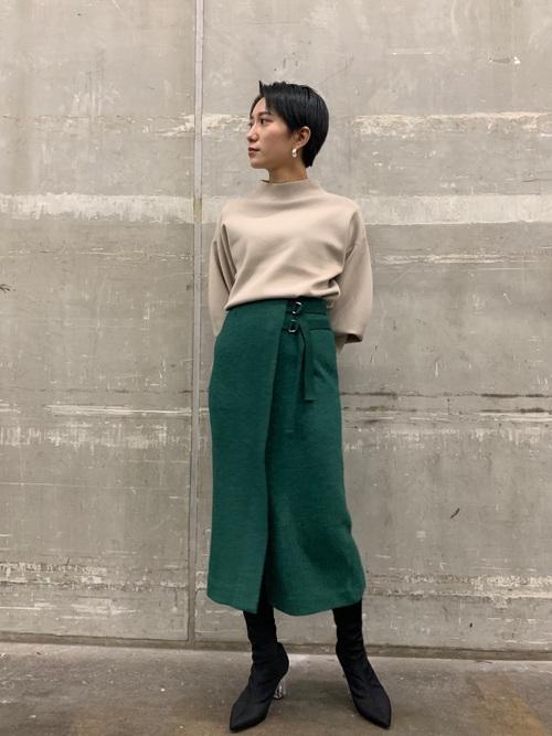 ベージュモックネックセーターと緑ウエストベルトタイトスカートと黒ブーツのコーデの女性
