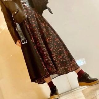 ライダースジャケットとコルセット風ベルトに黒地花柄ワンピを着た女性
