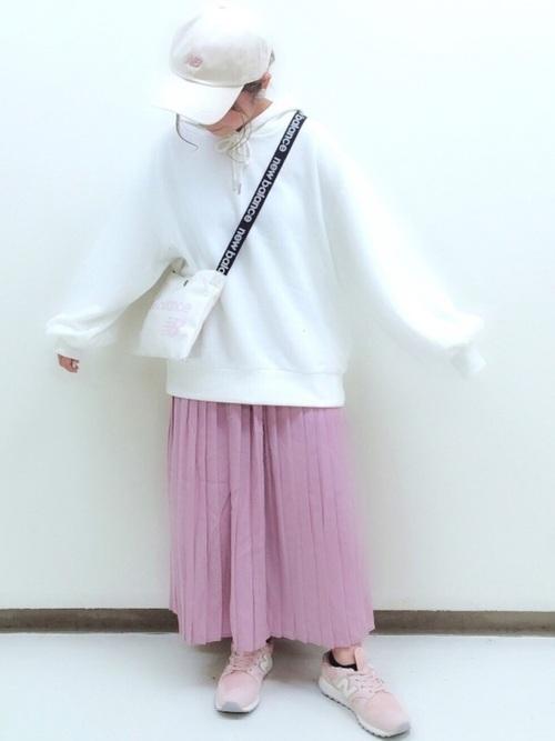 白パーカーとピンクプリーツシフォンスカートにピンクのニューバランススニーカーを履いた女性