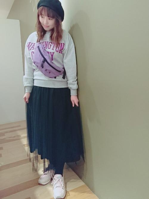 黒ベレー帽と黒チュールスカートにピンクのニューバランススニーカーを履いた女性