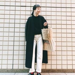 黒ロングノーカラーコートと白ハイウエストデニムパンツに黒ドレスシューズを履いた女性
