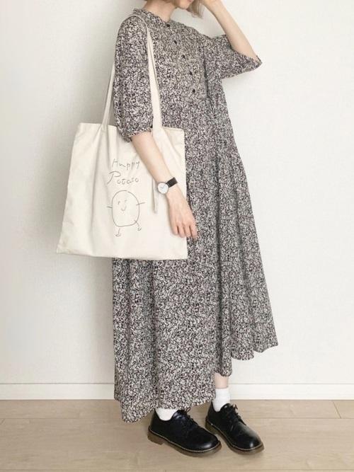 黒花柄ティアードマキシワンピースと白キャンパストートバッグに黒ドレスシューズを履いた女性