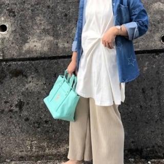 星柄デニムシャツと白ねじりディテールチュニックTシャツワンピースにベージュリブニットワイドパンツを履いた女性