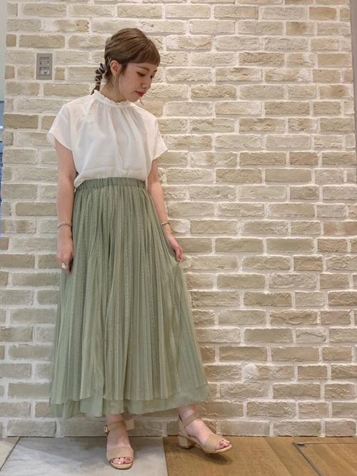 フェミニンスタンドカラー2Way白ブラウスと緑リバーシブルスカートとストラップサンダルのコーデの女性