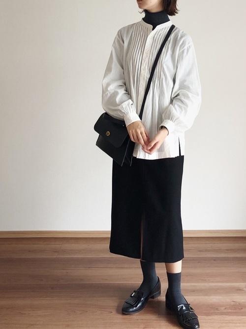 ピンタック白ブラウスと黒タートルニットとハイウエストポケットタイトスカートのコーデの女性