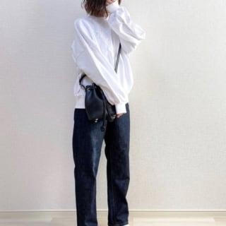 レース柄スウェットとネイビーパンツに白ソックスを履いた女性