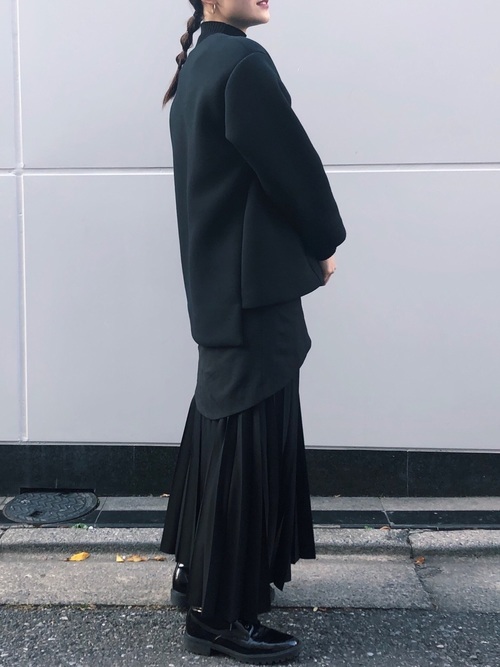 Vネックジャケットとロングスカートとブラックローファーのコーデの女性