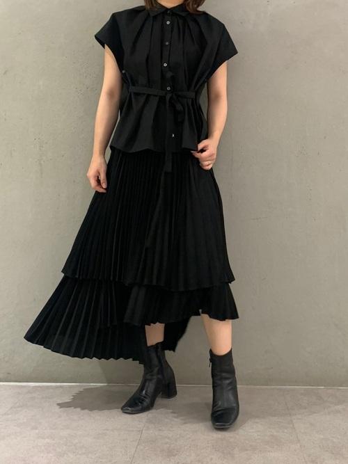 フレンチスリーブブラウスとレイヤープリーツスカートとミドルブーツのコーデの女性