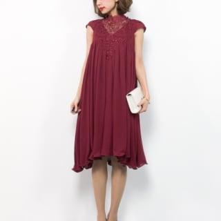 デコルテレースAライン赤ドレスとポインテッドトゥパンプスとウェストポーチバッグのコーデの女性